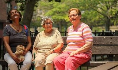3 elderly women sitting of a park bench, smiling.
