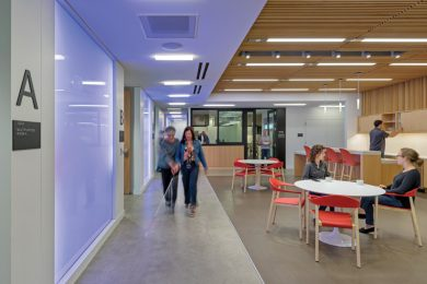 A blind individual with a walking stick, walking with a friend, in a building with inclusive design features