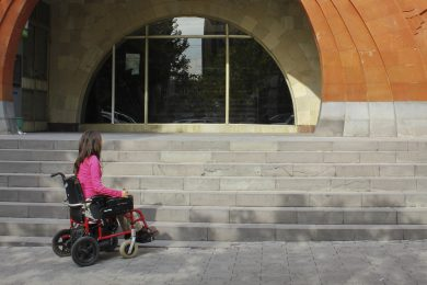 Image demonstrating a barrier by showing a wheelchair user looking at a staircase