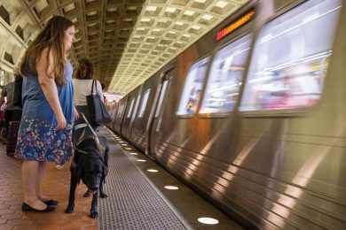 Claire Stanley waits at the Gallery Place – Chinatown Metro Station as the train arrives with her guide dog Kodiak on her commute home