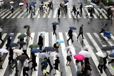 People holding umbrellas cross at crosswalks in the rain at Tokyo's business district
