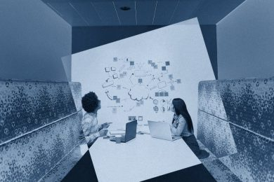 Male and female in a booth looking at wall that appears to have a diagram of their ideas