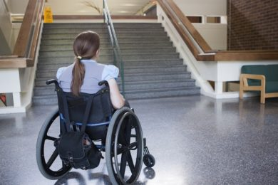 women in wheelchair looking at staircase
