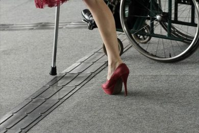 Red high heel and wheelchair wheel moving over tactile flooring