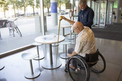 Man in wheelchair using a tape measure to measure the height of a table