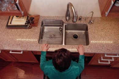 Universal design expert Rosemarie Rossetti aimed to create a home that she could function independently in while in her wheelchair. Image shows Rosemarie at her kitchen sink.
