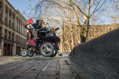 UW student Vanessa Link cruises up a sidewalk ramp in Pioneer Square while touring downtown Seattle with her motorized wheelchair to demonstrate the challenges.