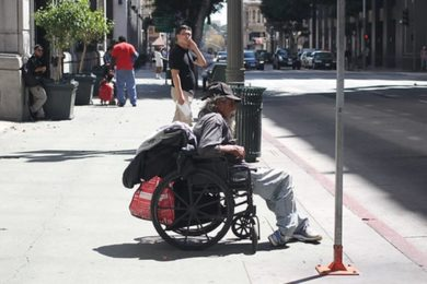Man in wheelchair sitting at a curb in a city
