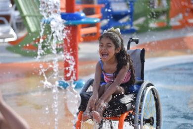 young girl in wheelchair splashing in water park