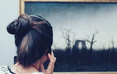 Back of a women's head listening to headphones