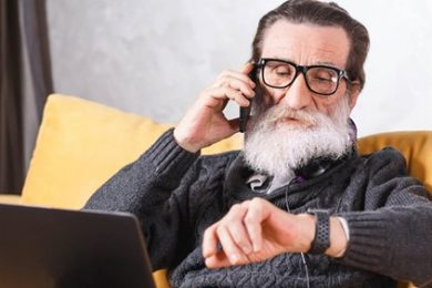 Elderly man talking on the phone, looking at his wrist watch, with a laptop siting on his lap.