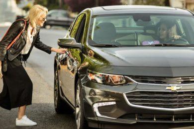 A women opening a car door to a lyft vehicle