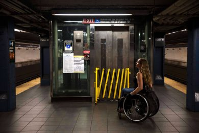 Women in a wheelchair, inside a transit station, with the elevator broken down.