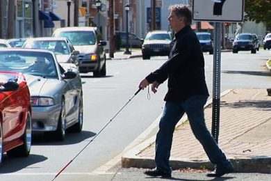 An individual using a white stick crossing the street
