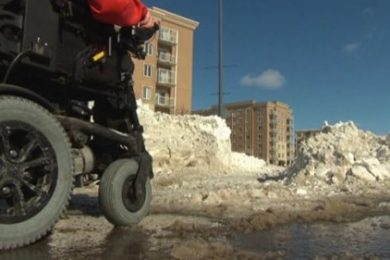 Power wheelchair on a path with snow and slush on the ground
