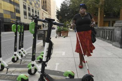 Scooters might be a hip fad, but they have also cluttered sidewalks and raised issues about ADA compliance. In this summer photo, Athalie Malone, who is blind, of the city's disability access advisory committee, navigates a crowded sidewalk.