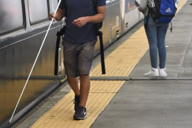 Individual walking on a tactile stip near a train with a white cane