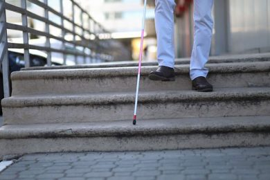 Feet walking down steps with a white cane