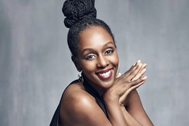 Stephanie Thomas, a Black woman with oval shaped eyes, round nose, smiling. Her chin is resting on her clasped hands. Her hair locs are pulled up in a high bun and wearing a sleeveless black top. The background is a grayish black backdrop. My condition's name is Symbrachydactyly. I am a congenital amputee missing digits on my right hand and feet.